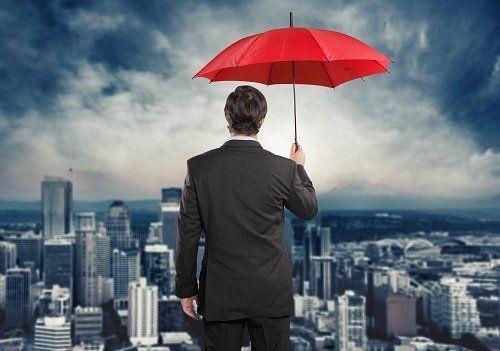 Un uomo di fronte alla città con un ombrello rosso