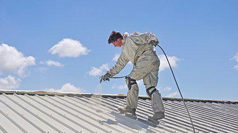 un uomo con una tuta che spruzza dell'acqua su un tetto