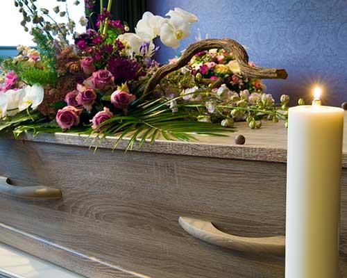 Fiori sulla bara e candela votiva