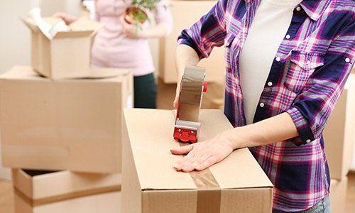 delle donne stanno chiudendo degli scatoloni una ha in mano un vaso con la pianta e l'altra sta chiudendo uno scatolone con lo scotch da imballaggio