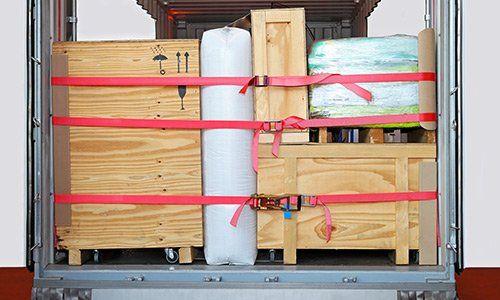 retro del rimorchio di un camion con dei mobili in legno all'interno, messi in sicurezza da una cinghia rossa che ne limita il movimento durante il trasporto