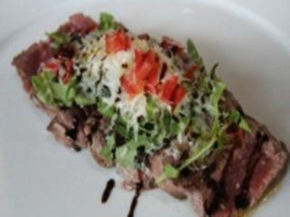 Sliced grilled sirloin steak with rocket and grana cheese