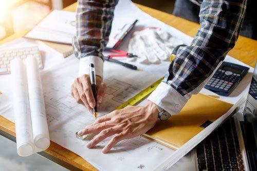 due mani di un uomo che scrivono su un foglio di un progetto