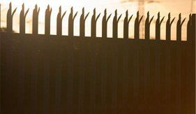 Sunlight coming through tall spiked security fencing