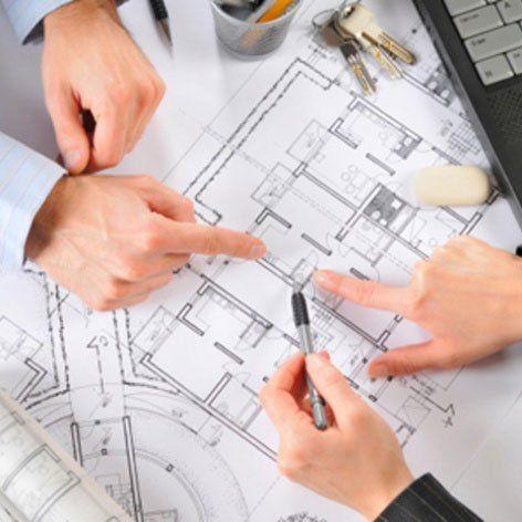 delle mani di alcune persone che indicano il disegno di un progetto-provincia di Trento
