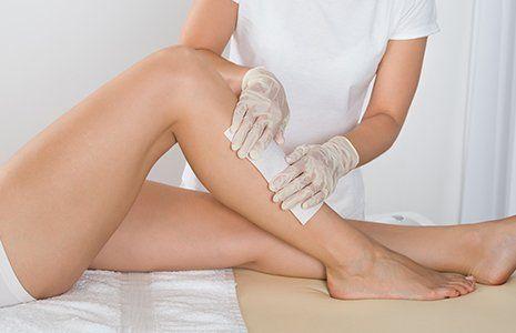 foto di una donna sdraiata con la gamba piegata in su e di un'altra con guanti che le sta applicando una striscia depilatoria