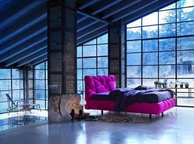 Una stanza con soffitto mansardato minimal, con un letto fucsia