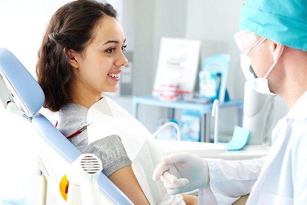 una ragazza sorridente sdraiata su un lettino e un dentista che le parla