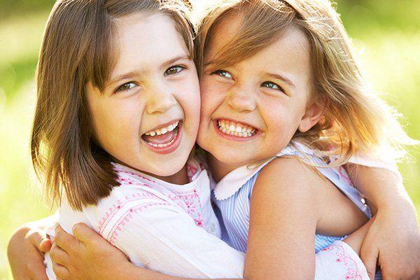 due bambine che si abbracciano e sorridono