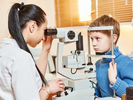 Optometrist examining the eyes of the kid