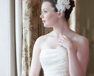 A bride in a white strapless gown, with a white flower in her hair
