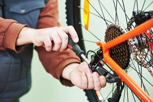 due mani che stanno avvitando con un cacciavite una corona della ruota posteriore di una bicicletta