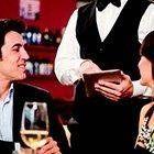 un cameriere che prende un ordine a due persone sedute al tavolo
