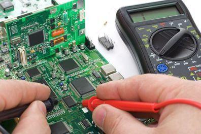 una mano e dei registratori di cassa disassemblati