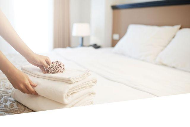 mani che sistemano asciugamani su letto di albergo controluce giorno