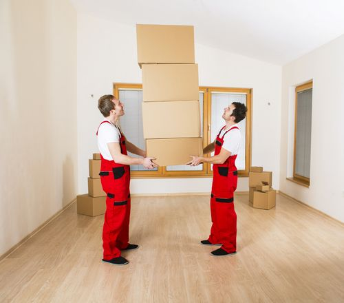Two movers holding a stack of boxes