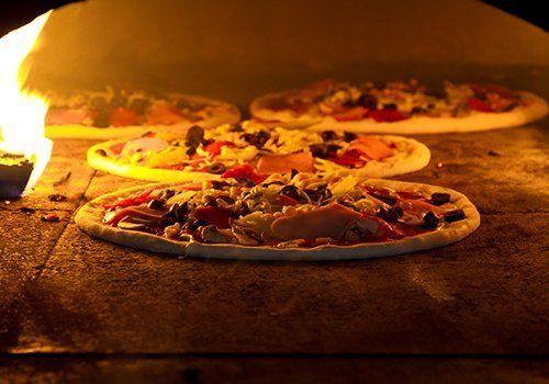 delle pizze in un forno a legna