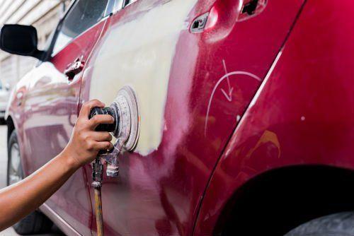 mano che vernicia una macchina rossa