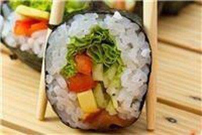 vista di un pezzo di sushi tra due bacchette