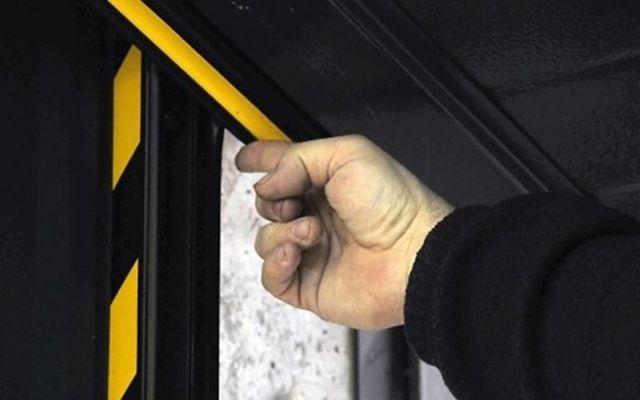 mano che segna un punto della porta di un garage