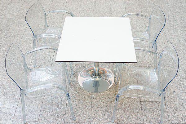 Un tavolino di color bianco e delle sedie in plexiglas