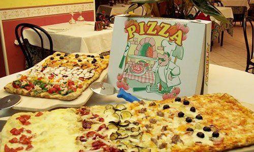 due pizze alle verdure a forme rettangolari sul tavolo e un taglia pizza e un cartone d'asporto anch'esso sul tavolo