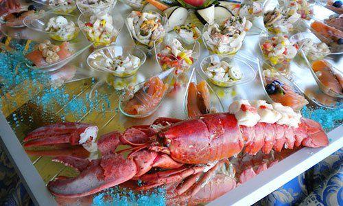 un'aragosta rossa e altre specialita' a base di pesce dentro a delle coppette di vetro su un tavolo di legno con del sale grosso blu
