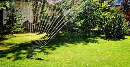 Sprinkler, installed by The Sprinkler Connection, watering lawn on a autumn day