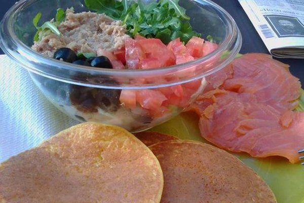 una bacinella di vetro con insalata,tonno, pomodori e olive nere, dei pancakes e delle fette di salmone