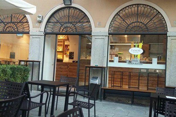 esterno di Lescrè con tavoli e sedie in ferro battuto e vista del bar con vetrine e rifiniture dei serramenti anch'esse in ferro battuto