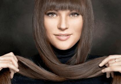 donna con frangia che si arrotola i capelli lunghi marroni