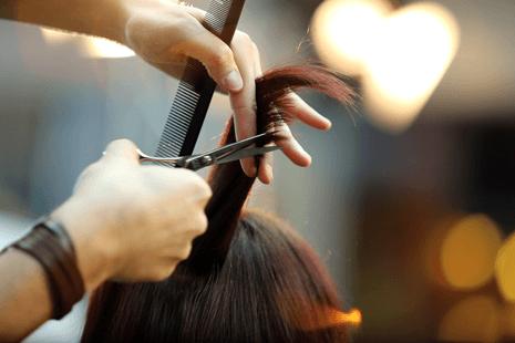 parrucchiere taglia i capelli a una cliente