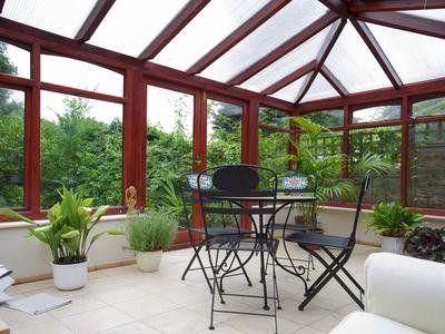 una terrazza con una struttura in legno con una pergola e vetri