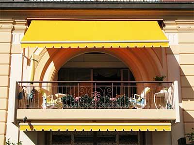 un balcone con una tenda da sole di color giallo