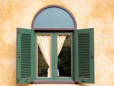una finestra ad arco con delle tapparelle in legno di color verde
