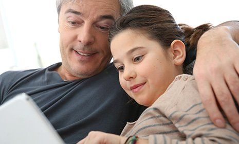 Father explaining her daughter in laptop