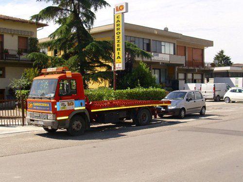 insegna carrozzeria LG con camion per soccorso stradale parcheggiato davanti alla ditta