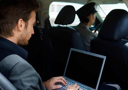 Individual travelling in a taxi and working on his laptop