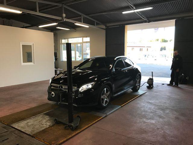Un meccanico con guanti bianchi e blu mentre controlla i livelli dell'olio di una vettura