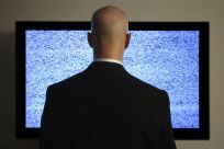 man standing in front of television static
