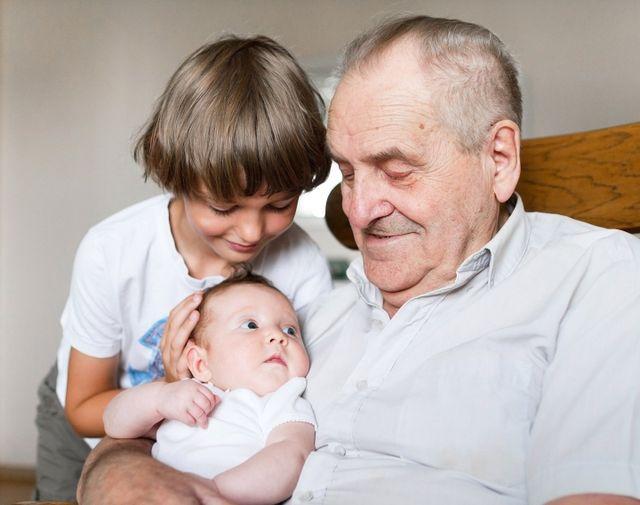 Un anziano con in braccio un neonato e un altro bambino a lato