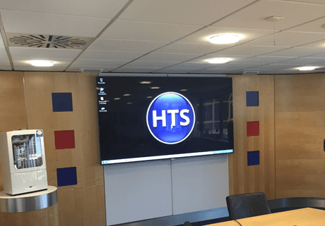 Meeting room with TV screen with HTS logo on it