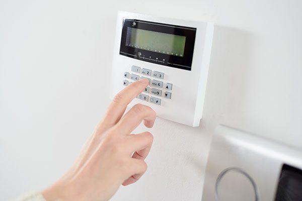 un dito che digita i tasti di una tastiera di un impianto di sicurezza