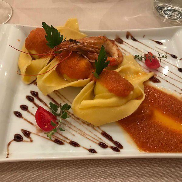 un piatto di ravioli con sugo e gamberi