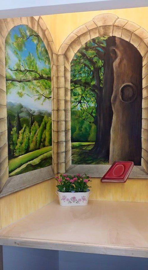 dipinto a muro raffigurante un arcata in pietra con il tronco di un albero sulla destra e diversi alberi verdi sulla sinistra
