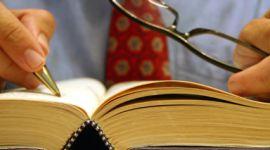 persona con cravatta e occhiali da vista in mano annota qualcosa su un libro