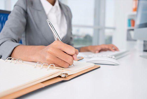 una mano di una donna che scrive su un'agenda