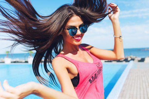 ragazza con i capelli al vento salta e sorride