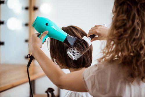 parrucchiera durante la piega a una cliente