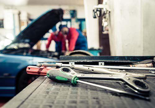 Primo piano di attrezzi da meccanico riposti su un tavolo e sullo sfondo sue meccanici all'opera
